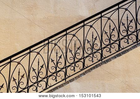 old stairs of concrete outdoors fragment of black steel railing with yellow walls perspective city architecture