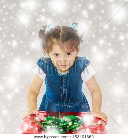 Caucasian little girl in a blue dress with short sleeves , kneeling around a red box with a bow. Close-up.Gray background with round white snowflakes.