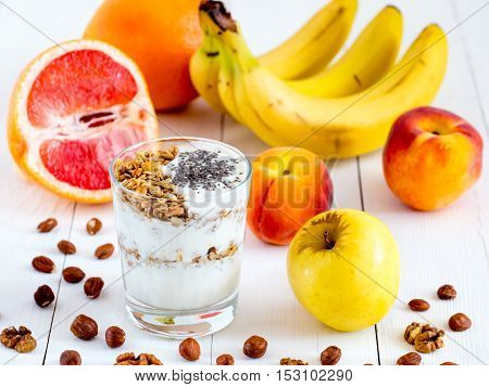 Healthy breakfast: yogurt with muesli and chia seeds, fruits and nuts on white wooden background. Dieting, healthy lifestyle concept meal