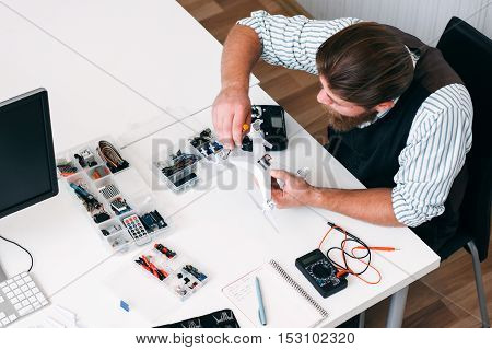 Top view on electrician workplace with tools, top view. Busy repairman fixing broken drone with screwdriver. Business, occupation, electronics construction concept