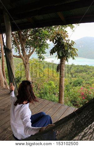 a casual happy woman relaxing on a hammock in the with seaview from a viepoint on Phi-Phi Island Krabbi Thailand