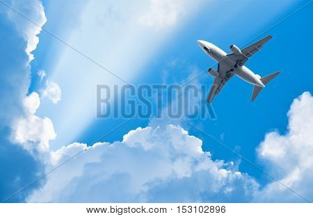 plane is flying among clouds in rays of sun