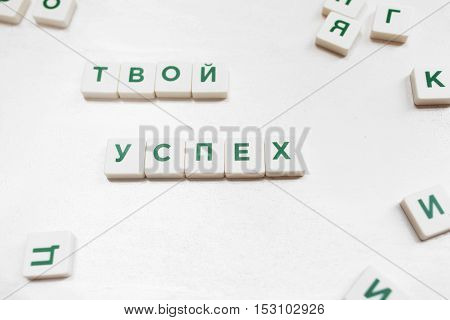 Your Success in russian, scrabble words. Crossword tiles on white background, business motivation, aspiration, incentive concept