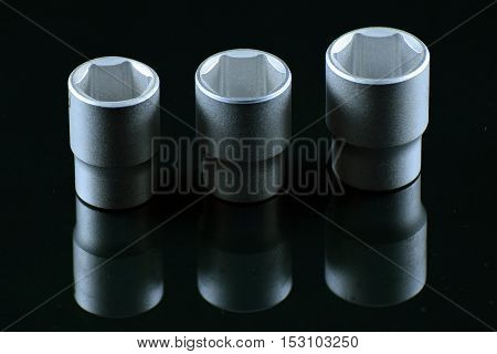Three sockets with black background and reflection.