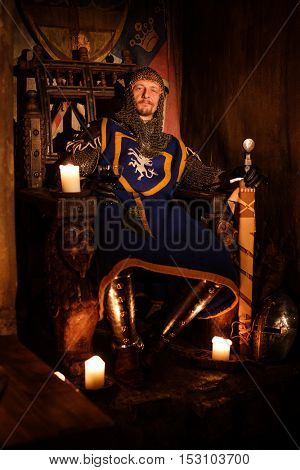 Medieval king on the throne in ancient castle interior.