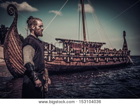 Viking warrior standing near Drakkar on seashore.