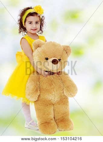 Joyful little girl Princess, dressed in a yellow dress, hugging a big Teddy bear. Standing at full height.white-green blurred abstract background with snowflakes.