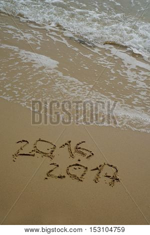new year numbers 2016 and 2017 drawings in the sand on the beach