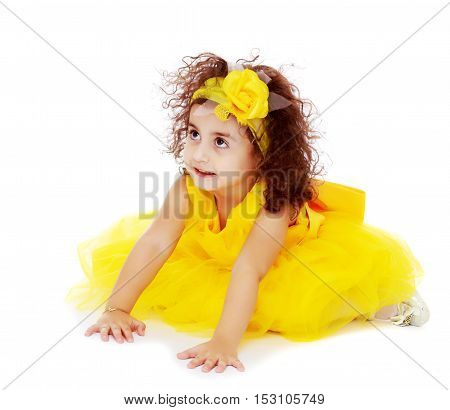 Funny curly little girl in a bright yellow elegant dress crawling on the floor. She looks to the top.Isolated on white background.