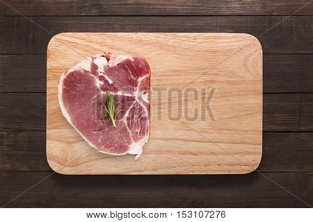 Top View Raw Pork Chop Steak On Cutting Board On Wooden Background. Copyspace For Your Text