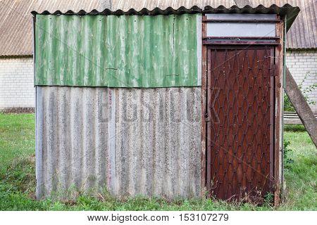 Old Weathered Barn With Metal Door.