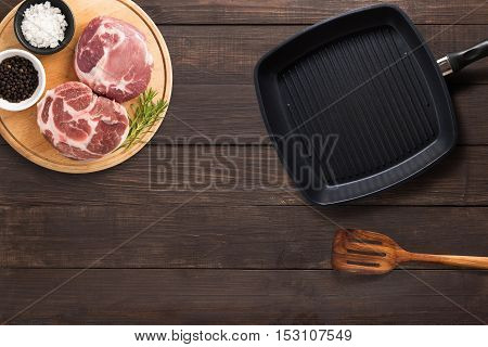 Top View Raw Pork Chop Steak, Grill Pan And Spatula On The Wooden Background. Copyspace For Your Tex
