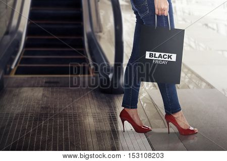Female shopper with Black Friday paper bag down from mall escalator