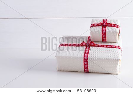 Two white gift boxes with polka dots with red ribbon