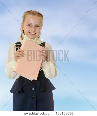 Happy girl schoolgirl in black dress and white blouse holding a textbook and smiling cheerfully at the camera. Close-up.On the pale blue background.