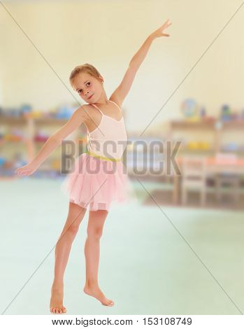 Charming little girl ballerina in a pink translucent dress.Against the background of a child's room .