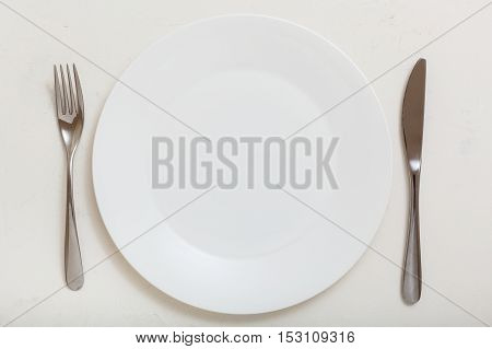 Top View Of White Plate With Knife, Spoon On White