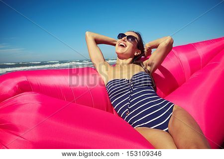 A fantastic woman grinning from ear to ear on the rose-colored inflatable boat on the beach enjoying gorgeous weather in her swimwear with blue and white stripes, also wearing brown-colored sunglasses