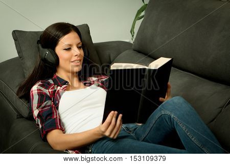 Pretty brunette girl reading and listening music on the sofa. Relax at home