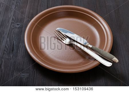 Brown Plate With Parallel Knife, Spoon On Dark