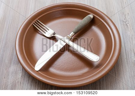 Brown Plate With Crossing Knife, Spoon On Gray