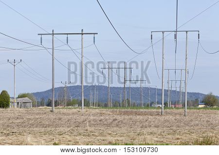 Power line in the landscape, wires and wooden pylon in the structure for electrical transmission. Village in a distance.
