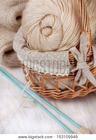 yarn ball in the basket knitting needles on a light wooden background