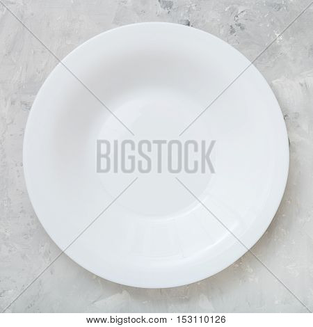 Above View Of White Deep Plate On Concrete Board