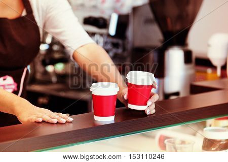 Young woman serving coffee to go. Close up concept.