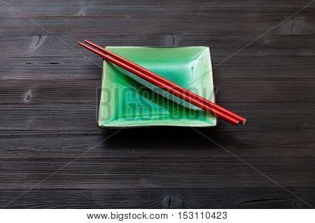 Green Saucer With Chopsticks On Dark Brown Board