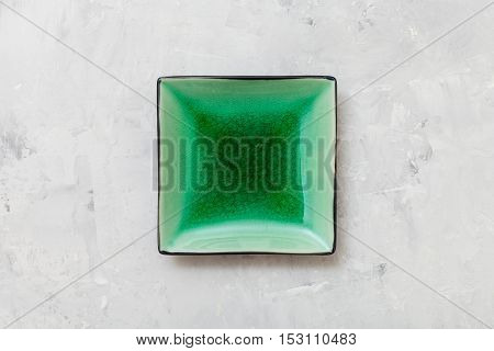 Above View Of Green Square Saucer On Gray Concrete