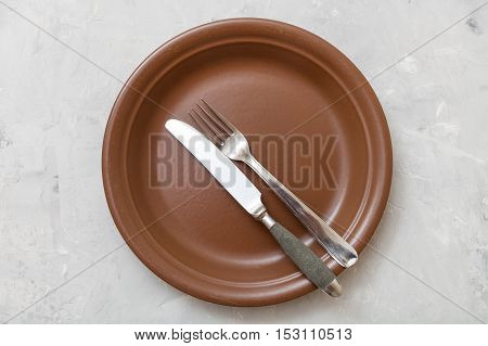 Top View Of Brown Plate With Flatware On Concrete