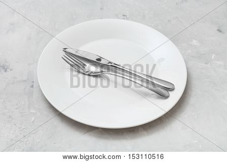 White Plate With Parallel Knife, Spoon On Concrete