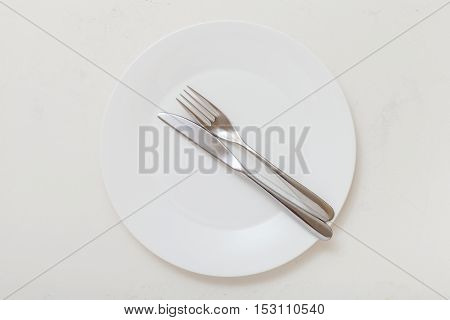 Top View Of White Plate With Flatware On White