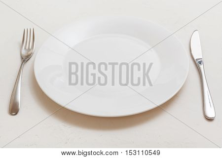 White Plate With Knife, Spoon On White Plaster