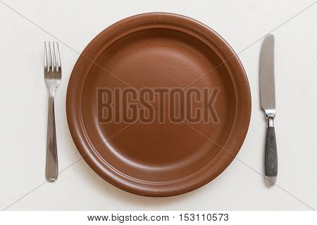 Top View Of Brown Plate With Knife, Spoon On White