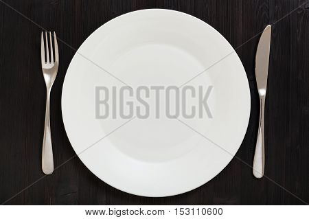 Top View Of White Plate With Knife, Spoon On Dark