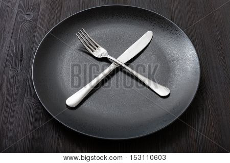 Black Plate With Crossing Knife, Spoon On Dark