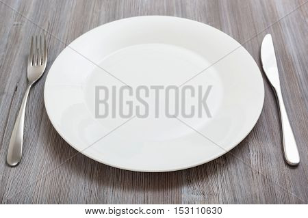 White Plate, Knife, Spoon On Gray Brown Table