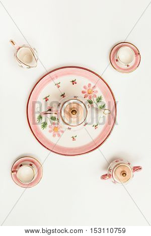 Top View Of Pink Porcelain Tea Set On White Paper
