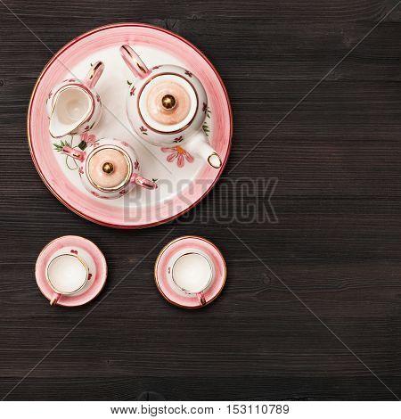 Top View Of Pink Tea Set On Dark Brown Board