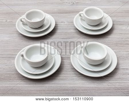 Four White Cups And Saucers On Gray Brown Table