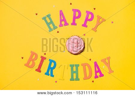 Words Happy Birthday with cupcake on yellow background.