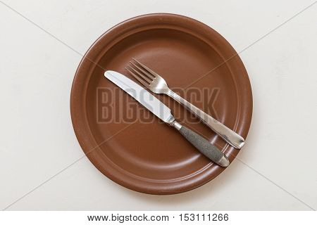 Top View Of Brown Plate With Flatware On White