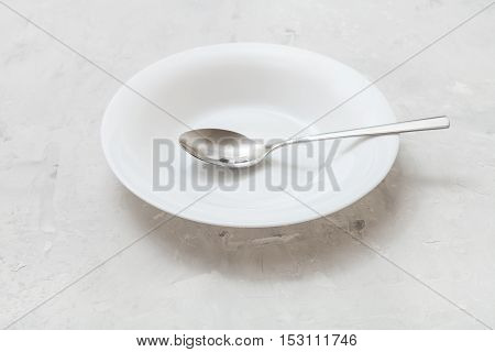 White Deep Plate With Steel Spoon On Gray Concrete