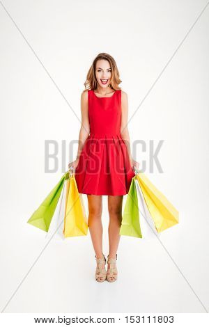 Full length portrait of a happy excited woman in red dress standing and holding colorful shopping bags isolated on a white background