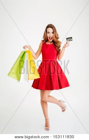 Portrait of a cheerful woman holding shopping bags and bank card isolated on a white background