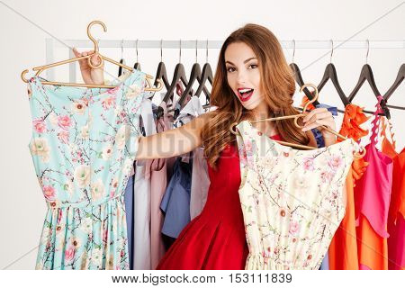 Portrait of a cheerful pretty woman in red dress choosing what dress to buy isolated on a white background