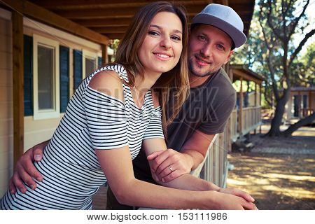 Side view shot of loving young couple holding hands and posing at the terrace. Wearing casual summer clothes. Being together during the vacation. The concept of rest and relaxation