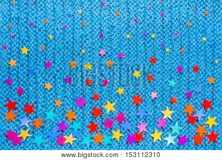 Colorful stars of different sizes on a blue knit background. New year and Christmas background.